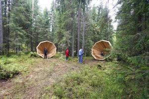 People gather near the wooden megaphones in the forest near Pahni village